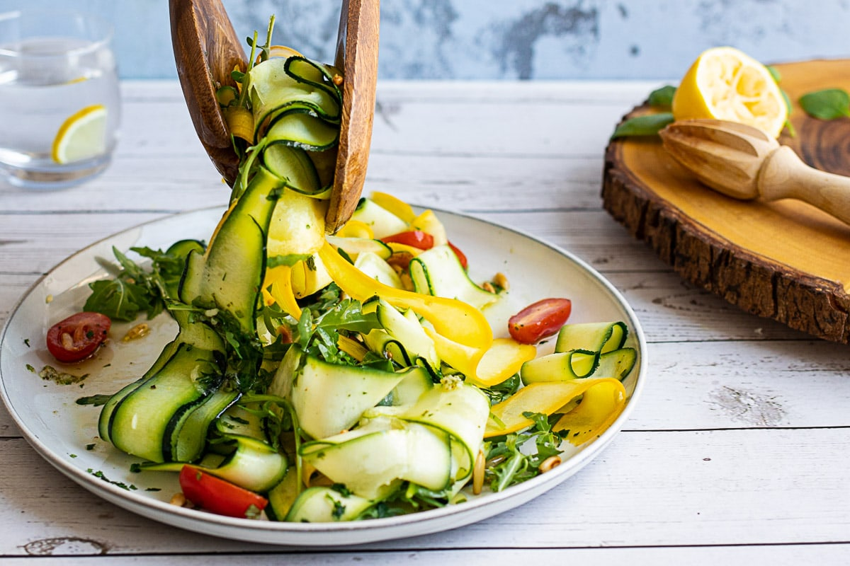 Courgette Salad being picked up by wooden servers
