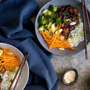 Teriyaki chicken donburi with chopsticks and sesame seeds