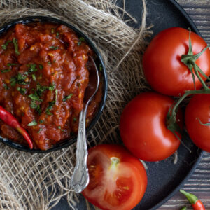 Tomato chutney in a bowl next to tomatoes and chillis