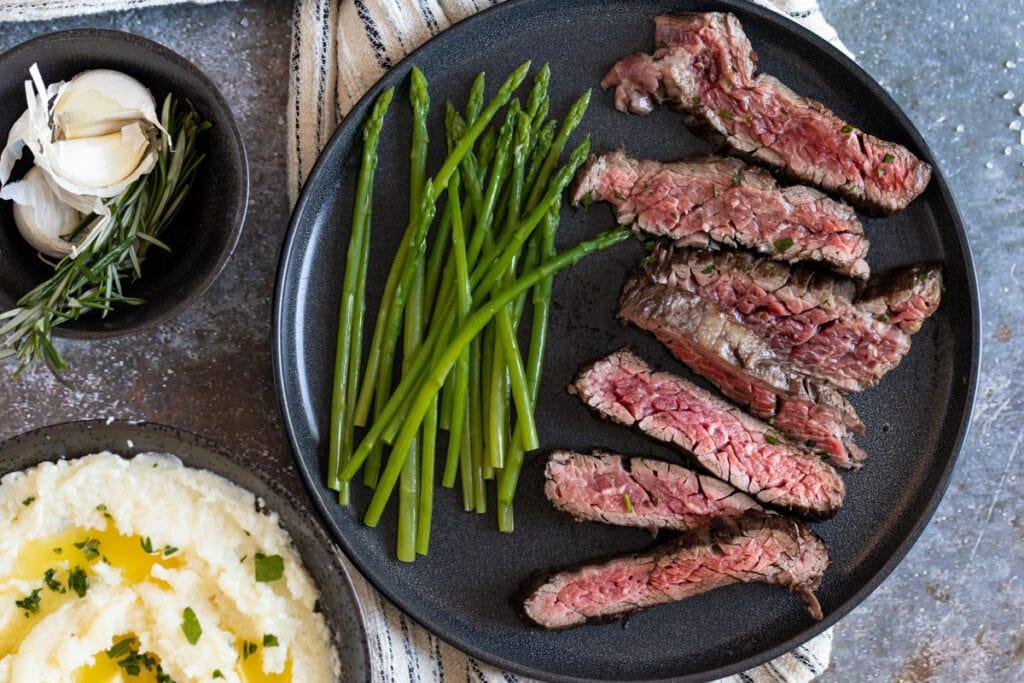 Bavette steak sliced on a plate with asparagus