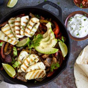Halloumi fajitas in a pan with tortillas and sour cream