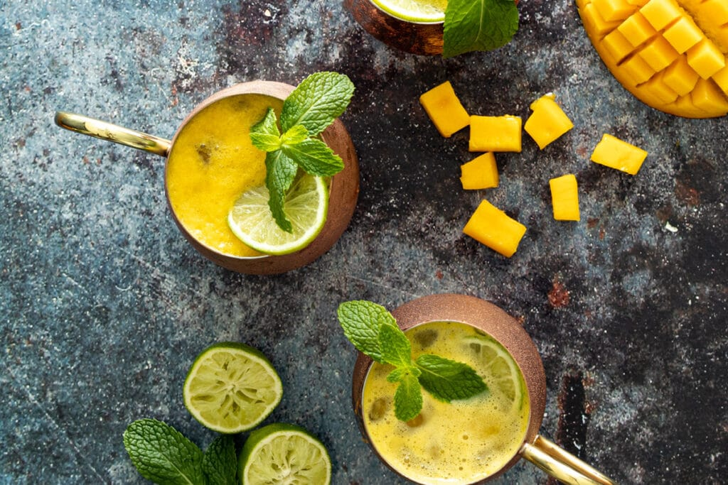 Looking down at mango mules with mango and limes scattered around