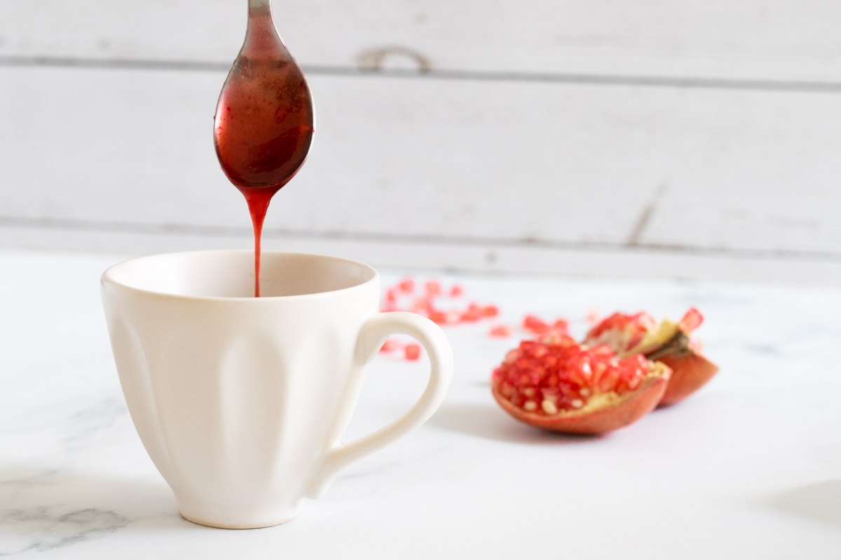 Pomegranate Molasses dripping from a spoon into a cup