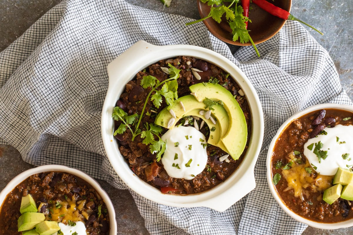 Slow cooker chilli con carne in a bowl with avocado